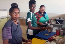 Three young Aboriginal women preparing food in a kitchen