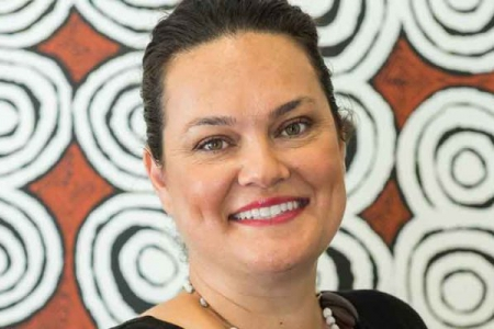 Close-up of Kristy Masella in front of an Aboriginal painting