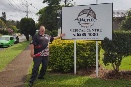 Man standing proudlly in front of a sign for Werin Aboriginal Corporation