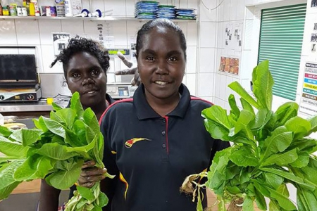 Two young women in a shop holding salad greens
