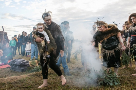 Darug traditional custodians with furs, feathers and ochre body paint in a smoking ceremony