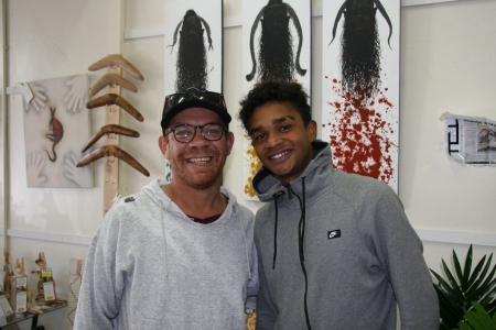 Two young men smiling to camera in an art shop